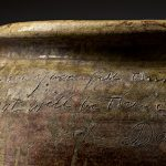 Detail image of a brown earthen ware pot with inscription carved into the side near the lip.