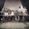 photograph of a sepia-tones tapestry with photo-realist depiction of group of black men and women at a large heavy wooden table holding weapons