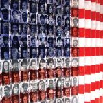 "Close-up of the ""Flag of Faces"" exhibit at Ellis Island showing black and white photos of people superimposed on red, white, and blue tiles."
