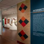 image of interior of an art exhibition with panel in the foreground and various textiles in the background