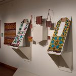 Photograph of the wall of an exhibition space with brightly-colored textiles and beadwork displayed against a white wall