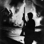 Black and White Image of the outline of a soldier holding a gun in front of a burning building