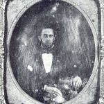 Black and white image of a daguerreotype in an ornate frame: portrait of a black man in the 19th century wearing a suit and bow tie.