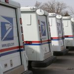 A photograph of USPS delivery trucks parked in a parking lot.