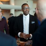 color image of a Black man with glasses dressed in a suit holding a drink in both hands speaking with a group at an event