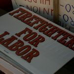 "A stack of posters reading ""FIREFIGHTERS FOR LABOR"""