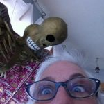 Interestingly cropped photograph portrait of artist Jo Jensen. Part of her face (just bespeckled eyes and top of her white hair) appear in the right-hand forefront while one of her skull sculptures appears looming in the background.