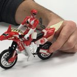 closely cropped image of a man's hand holding a toy: a red power ranger on a motorcycle.