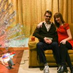 two people sit on a mid-century modern couch next to the installation of an Evergleam Christmas tree.