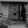 A man stands on a porch in a film still