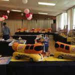 image of a table with Oscar Mayer memorabilia and 2 wienermobiles
