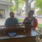 man and woman in sunglasses stand behind a Hammond organ on an outdoor porch