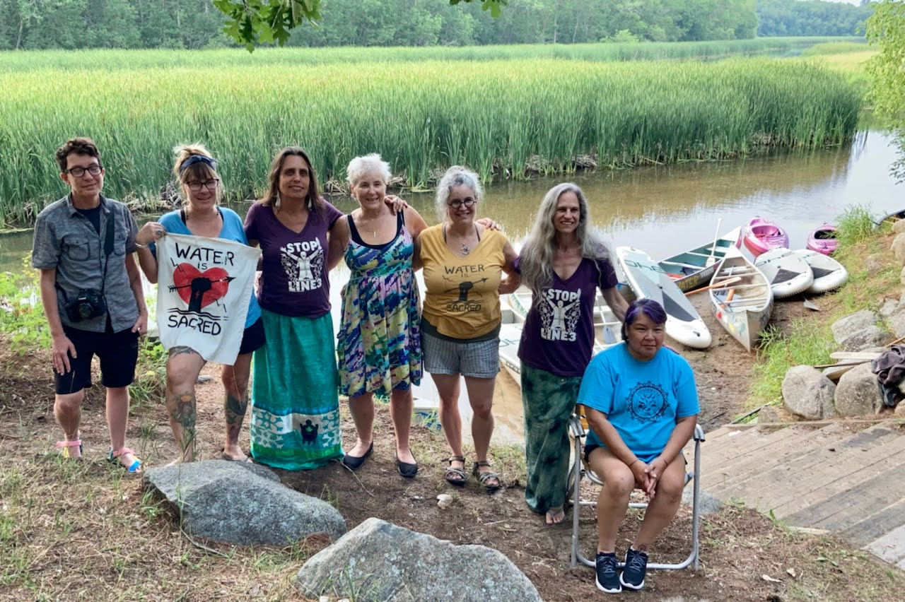 Seven people stand in front of a river holding signs that say Water is Sacred and wearing shirts that say Stop Line 3
