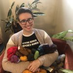 Image Description: A white, queer woman with black framed glasses sits in a red chair, smiling and holding a bunch of brightly colored skeins of yarn. She is surrounded by various sizes of green and white house plants.